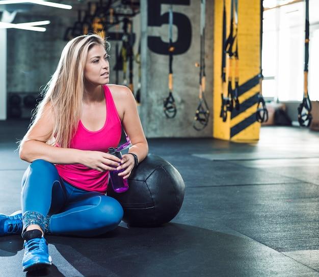 Piękna kobieta relaksuje po wykończeniowego treningu w sprawność fizyczna klubie