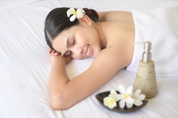 Piękna kobieta relaksuje się i ma masaż w uzdrowisku