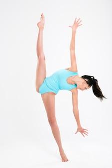 Piękna kobieta robi akrobatyczny wyczyn na białym tle na białej ścianie