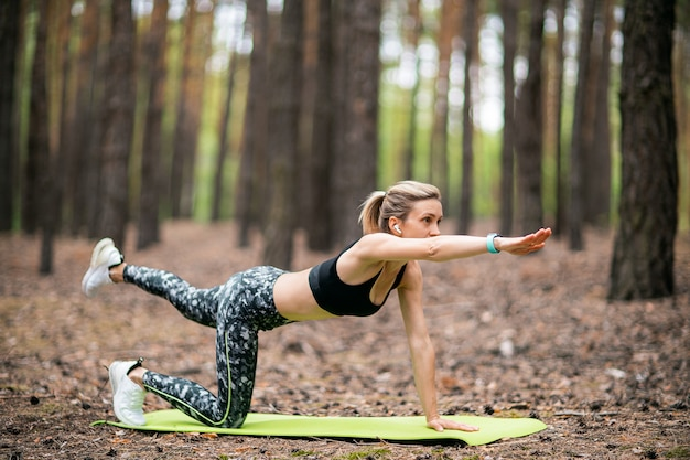 Piękna kobieta robi joga w lesie. koncepcja ćwiczeń i medytacji. drewno sosnowe w letnim motywie.