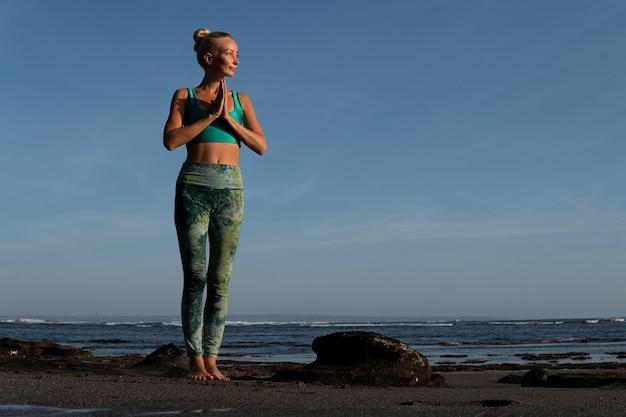 Piękna kobieta robi jogę na plaży