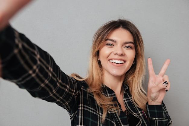 Piękna kobieta robi selfie i pokazuje pokoju gest z palcami
