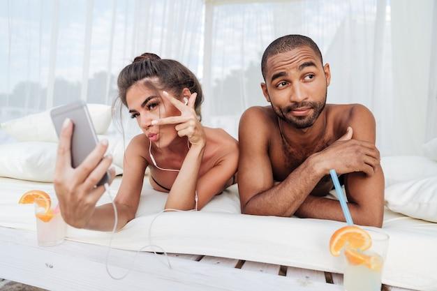 Piękna kobieta robi selfie ze smartfonem z niezadowolonym afrykańskim mężczyzną na plaży