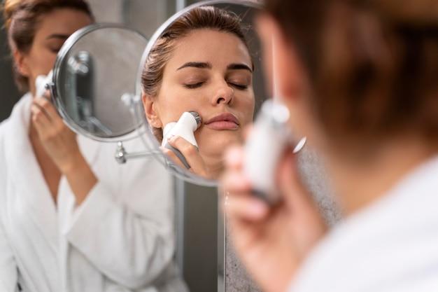 Piękna kobieta robi sobie masaż twarzy