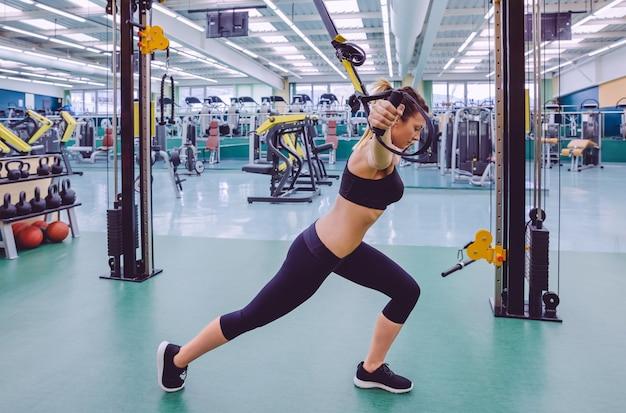 Piękna kobieta robi twardy trening zawieszenia z pasami fitness w centrum fitness. koncepcja zdrowego i sportowego stylu życia.