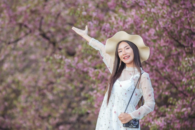 Piękna kobieta robi zdjęcie kamerą w ogrodzie kwiatowym sakura.