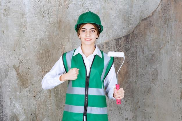 Piękna kobieta robotnik budowlany ze stojącą rolką do malowania