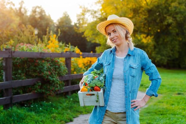 Piękna kobieta rolnik w kapeluszu z pudełkiem świeżych ekologicznych warzyw
