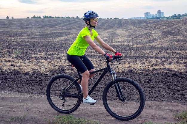 Piękna kobieta rowerzysta jeździ na rowerze na polu.