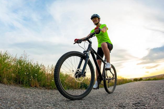 Piękna kobieta rowerzysta jeździ rowerem na drodze.