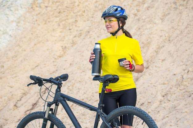 Piękna kobieta rowerzysta na żółto z herbatą i termosem w ręku