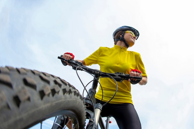 Piękna kobieta rowerzysta w kolorze żółtym czekamy, trzymając rower