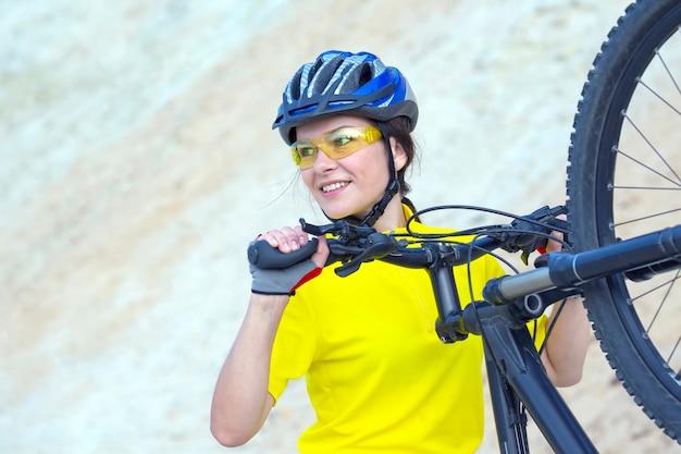 Piękna kobieta rowerzysta z rowerem przed piaskiem. sport i rekreacja.