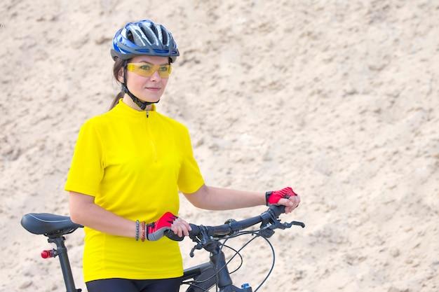 Piękna kobieta rowerzysta z rowerem