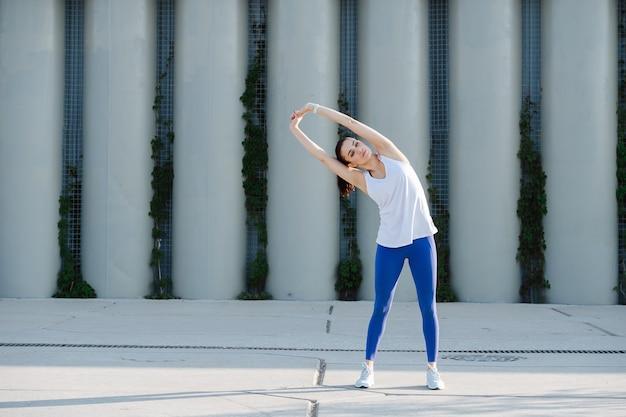 Piękna kobieta rozciągająca się na betonowej kostce robiąca boczne skłony