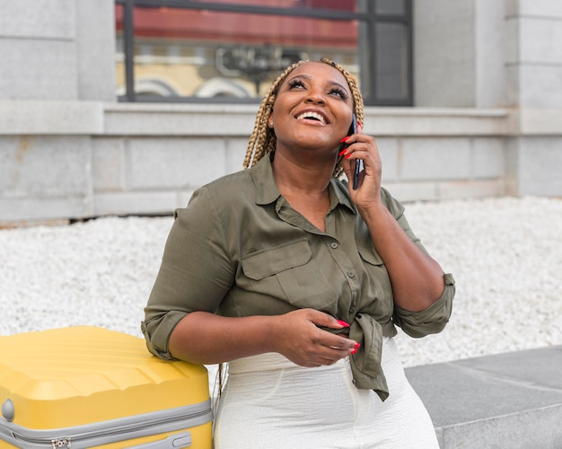 Piękna kobieta rozmawia przez telefon obok swojego żółtego bagażu