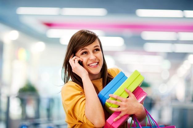 Piękna kobieta rozmawia przez telefon w centrum handlowym