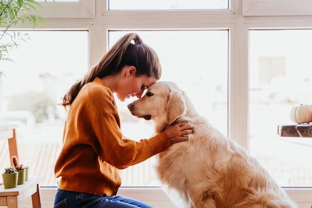 Piękna kobieta ściska jej uroczego golden retriever psa w domu. koncepcja miłości do zwierząt. styl życia w pomieszczeniu