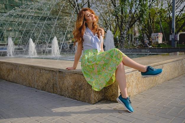 Piękna kobieta siedzi blisko fontanny