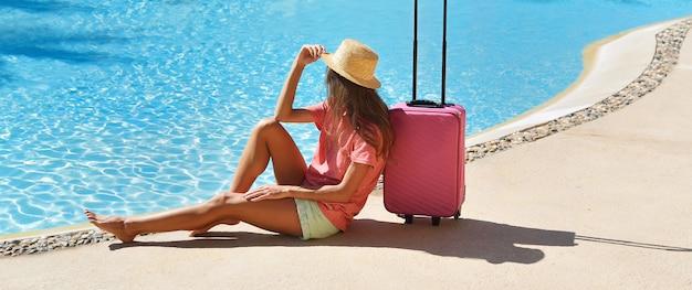 Piękna kobieta siedzi blisko różowej walizki blisko pływackiego hotelowego basenu terenu. podróże, wakacje letnie