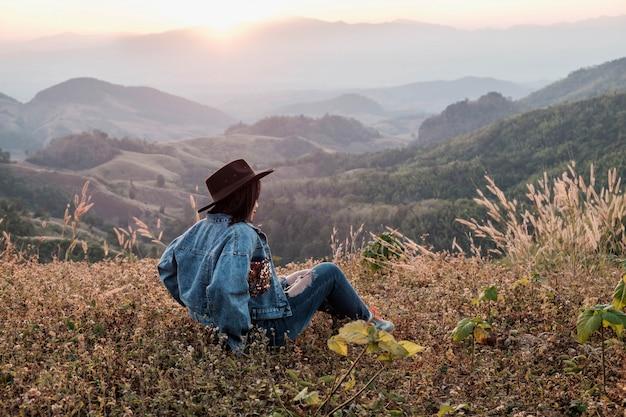 Piękna kobieta siedzi i cieszy się widokiem na góry