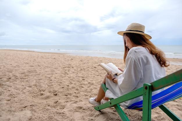 Piękna kobieta siedzi i czyta książkę na leżaku z uczuciem relaksu
