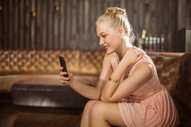 Piękna kobieta siedzi na kanapie i przy użyciu telefonu komórkowego