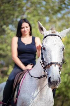 Piękna kobieta siedzi na koniu i głaszcze ją. szkolenie jeździeckie