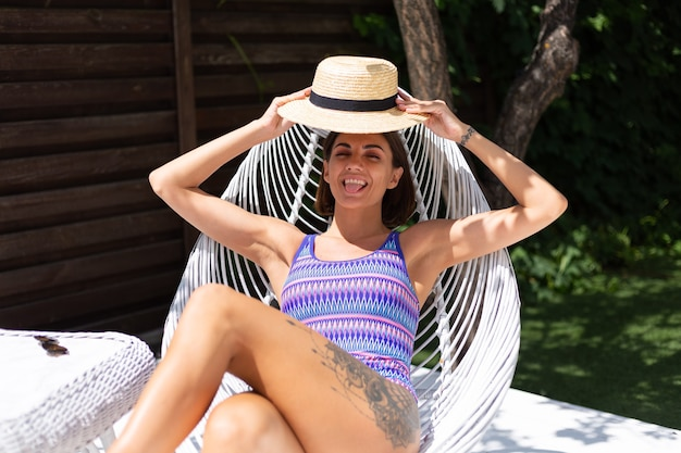 Piękna kobieta siedzi na krześle na podwórku w letni słoneczny dzień, ciesząc się niesamowitą ciepłą pogodą, łapiąc promienie słoneczne