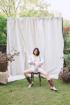 Piękna kobieta siedzi na krześle w ogrodzie.