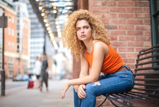 Piękna kobieta siedzi na ławce, czekając na coś