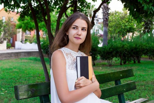 Piękna kobieta siedzi na ławce i myśleć o coś trzyma książkę w parku