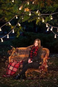 Piękna kobieta siedzi na ławce w jesiennym parku