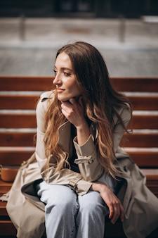 Piękna kobieta siedzi na ławce z piegami