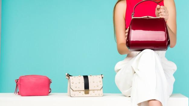Piękna kobieta siedzi na ławce z trzy torebka kiesa
