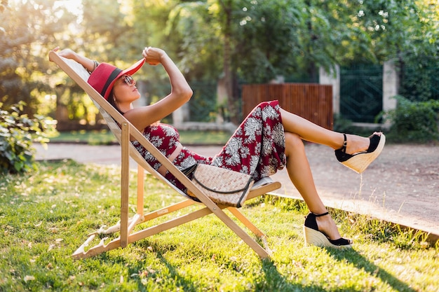 Piękna kobieta siedzi na leżaku w tropikalnym stroju. pani w letnim trendzie mody ulicznej. w torebce ze słomy, czerwonym kapeluszu, okularach przeciwsłonecznych. stylowa dziewczyna uśmiecha się w radosnym nastroju na wakacjach.