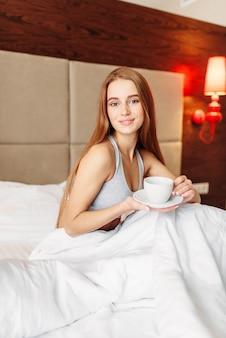 Piękna kobieta siedzi na łóżku przy filiżance kawy, dzień dobry. dziewczyna budzi się w sypialni