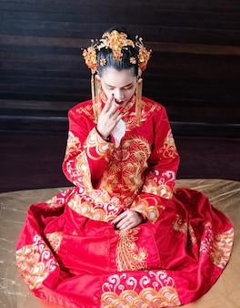 Piękna kobieta siedzi na parterze, ubrana w chiński kostium, portret modelki, festiwal noworoczny