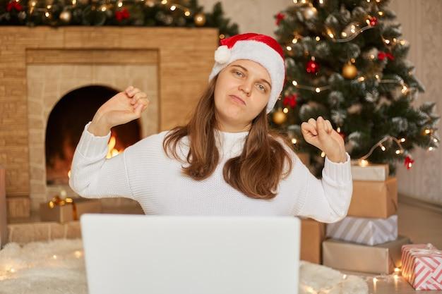 Piękna kobieta siedzi na podłodze pracując z laptopem w domu wokół choinki, rozciągając plecy, zmęczona i zrelaksowana, dziewczyna ubrana w biały sweter i czapkę świętego mikołaja.