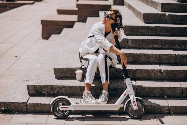 Piękna kobieta siedzi na schodach z jej skuter