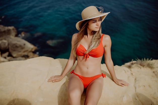 Piękna kobieta siedzi na skale i patrząc na morze.