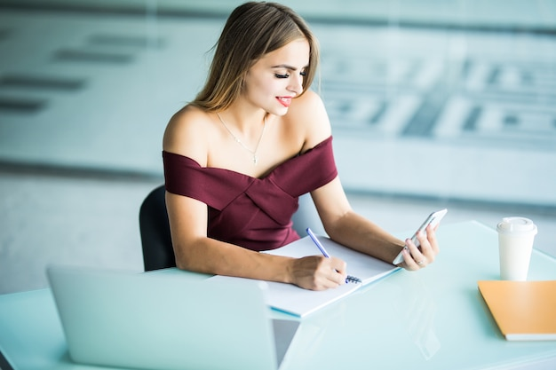 Piękna kobieta siedzi przy biurku w biurze