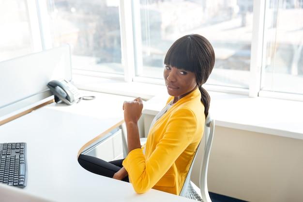 Piękna kobieta siedzi przy stole w biurze i odwraca wzrok