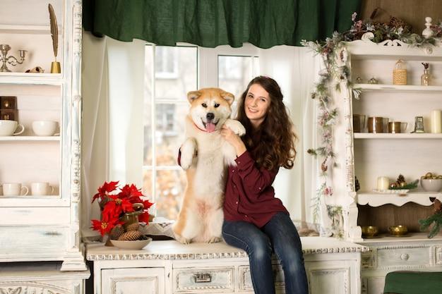 Piękna kobieta siedzi retro drzewnego kredensu. przytula, przytula swojego psa akita inu.