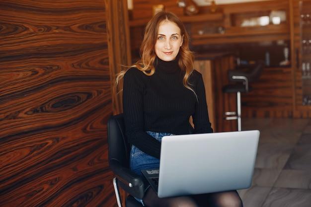 Piękna kobieta siedzi w domu z laptopem