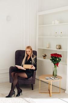 Piękna kobieta siedzi w fotelu i otwierając pudełko, patrząc do środka