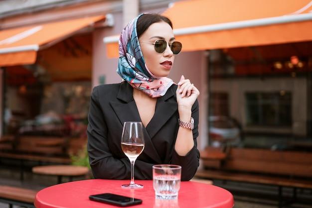 Piękna kobieta siedzi w kawiarni na ulicy przy lampce wina