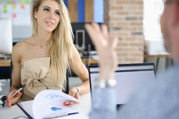 Piękna kobieta siedzi w miejscu pracy, patrząc zainteresowany