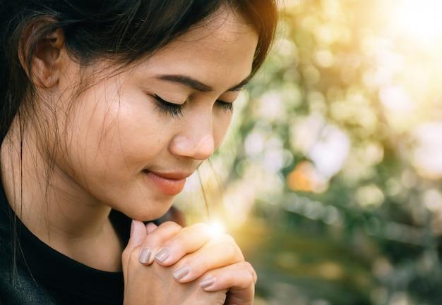 Piękna kobieta siedzi w modlitwie.