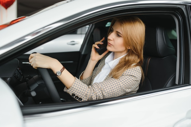 Piękna kobieta siedzi za kierownicą samochodu